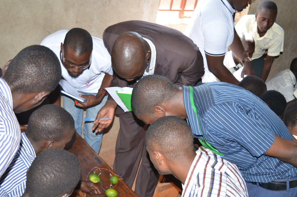 Judges observe a lemon battery that students made.JPG