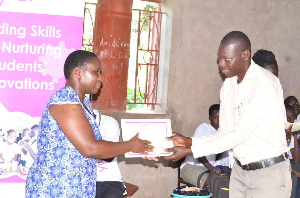 The D.E.O givings out a certificate to one of the Yiya educators.JPG