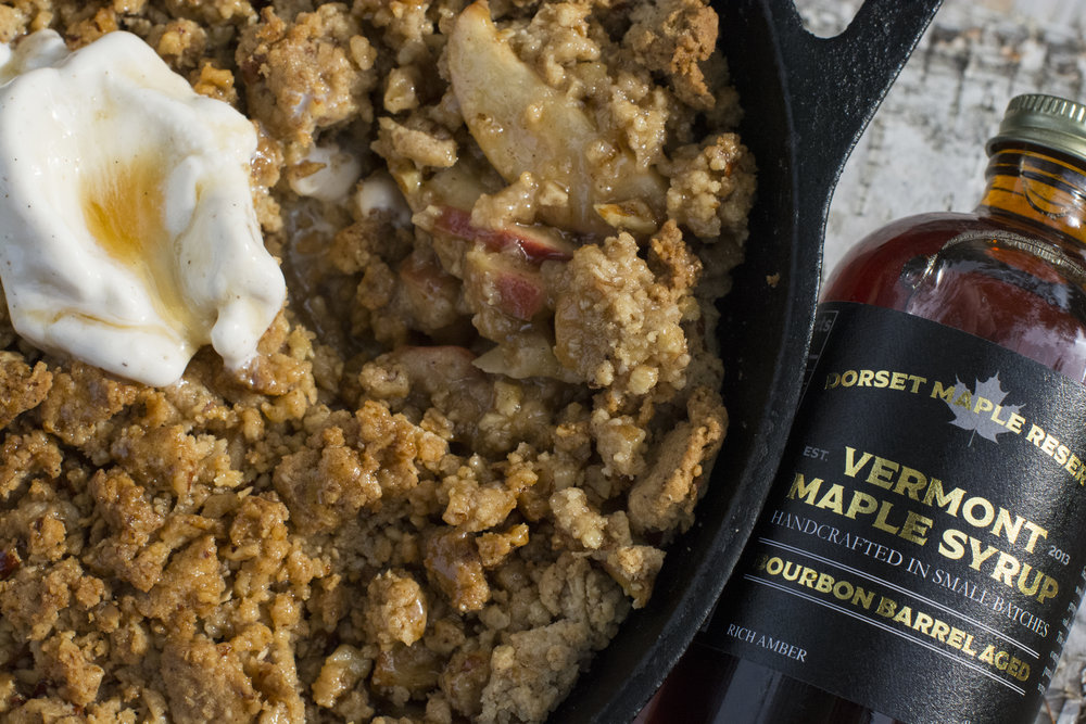 Cast Iron Bourbon Apple Crisp - 3 Apples (Granny Smith or Fuji)1 tablespoon fresh lemon juice5 tablespoon  bourbon 4 tablespoon turbinado sugar1 teaspoon cinnamon 1 1/2 cup granola 1/2 cup rolled oats5 tbl softened butterheavy pinch of kosher saltPreheat oven to 350 degrees, core and slice apples thinly. In a large bowl combine the apples, lemon juice, bourbon, sugar and cinnamon. Toss to coat evenly. In another bowl combine softened butter, granola, and oats. Place apples in a 10 in greased cast iron skillet and top with granola mixture. Bake for 30-40 minutes or until the top is browned and the apples are soft. Serve with good quality vanilla ice cream and a heavy drizzle of Dorset Maple Reserve Bourbon Barrel Aged maple syrup.