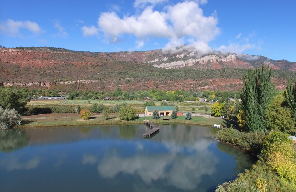 We're for Outdoors - Being set in the Animas Valley means we get to enjoy the mountain ridge lines to the east and to the west. This image looks westward and shows our private lake with the event center on the far side. This lake is great for paddle boating, kayaking, stand-up paddle boarding, or just dangling your feet off the dock.