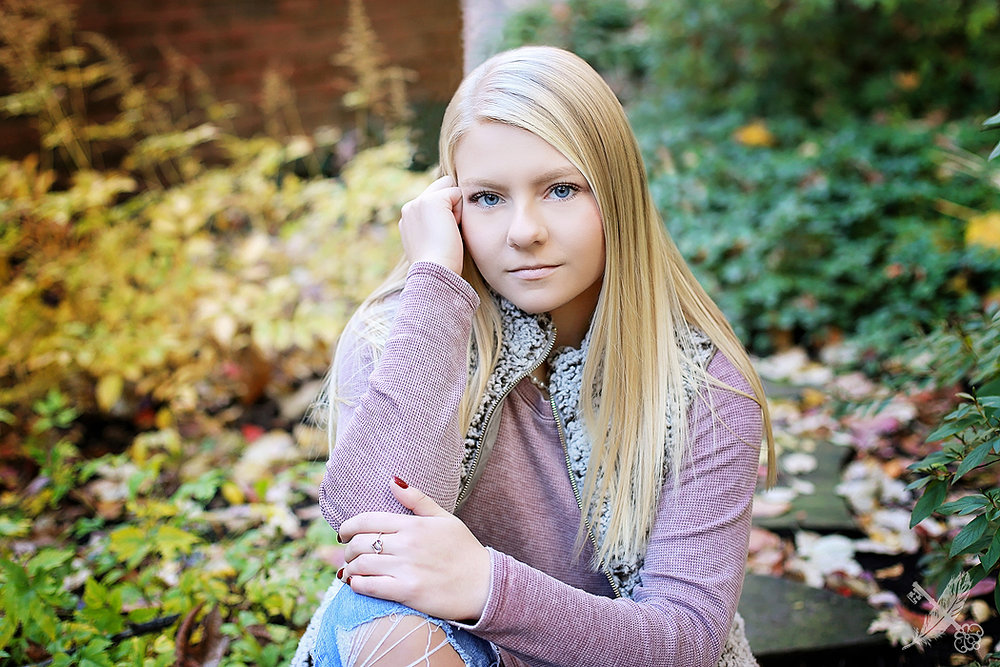 Huntington north high school senior, Emma sitting in a natural environment for her senior pictures with feather and key photography.