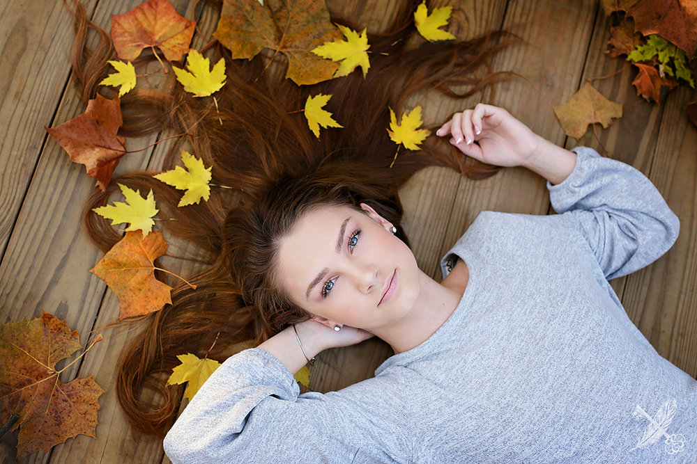 Huntington North senior Kaitlyn lays in yellow leaves for her senior pictures with feather and key.