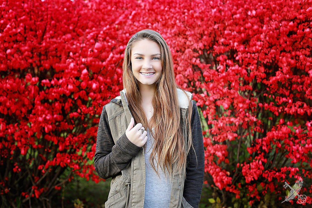 Huntington Senior in front of vibrant red trees for senior pictures with feather and key photographer.