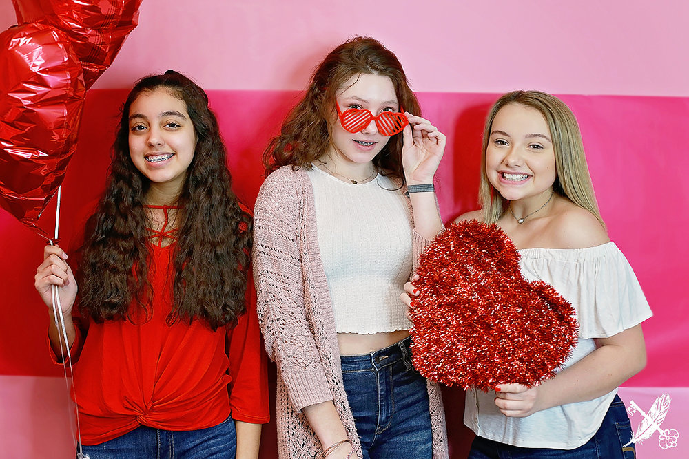 Central Noble seniors and HNHS seniors hold valentines day hearts and balloons in a galentines day themed photo shoot in the feather and key studio huntington.