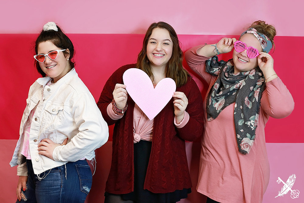 Norwell and HNHS seniors pose with heart shaped props at the feather and key studio in huntington.