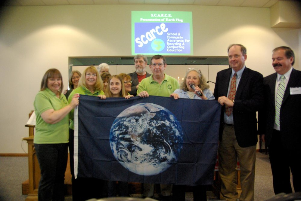 The Green Disciples of the First United Methodist Church of West Chicago accept the Earth Flag from Kay McKeen of S.C.A.R.C.E