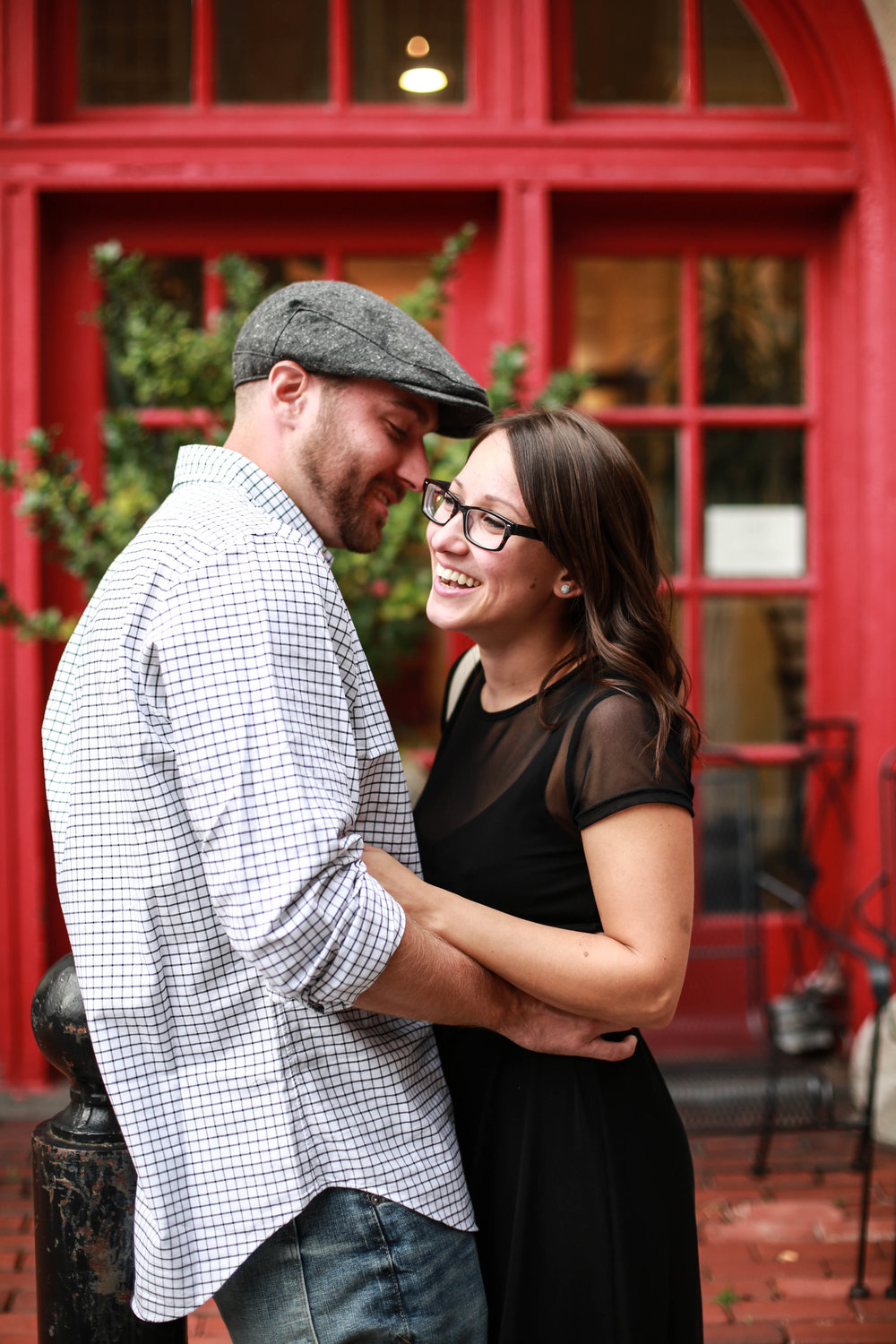 Laughing couple in front of a red building