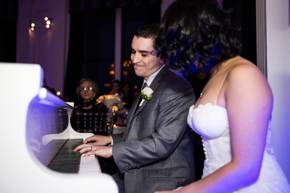 Groom is playing piano for his bride at the Downtown club