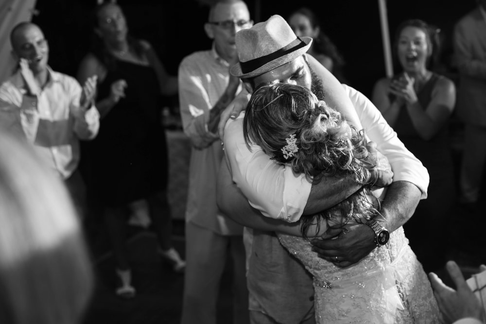 Bride and groom hugging each other at their wedding reception