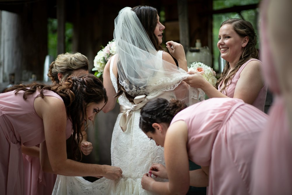 bridesmaids help bustle the dress