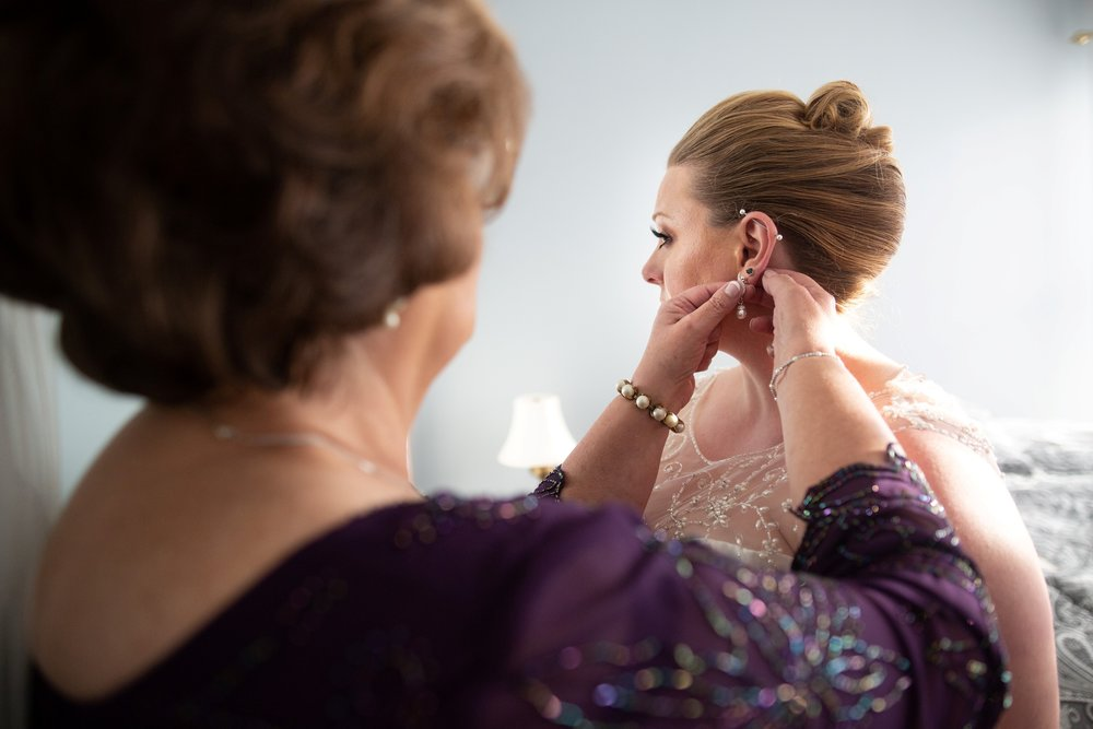 bride's mother putting earrings on