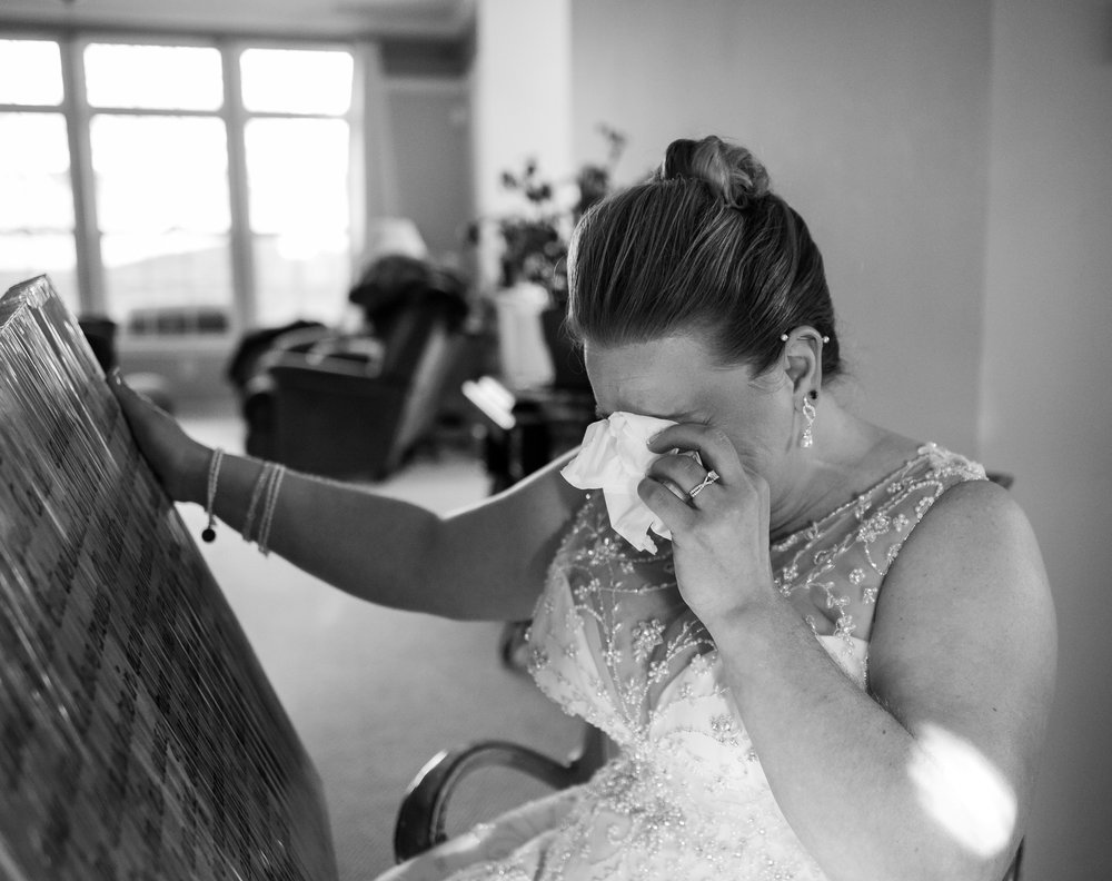 bride crying after opening gift from groom