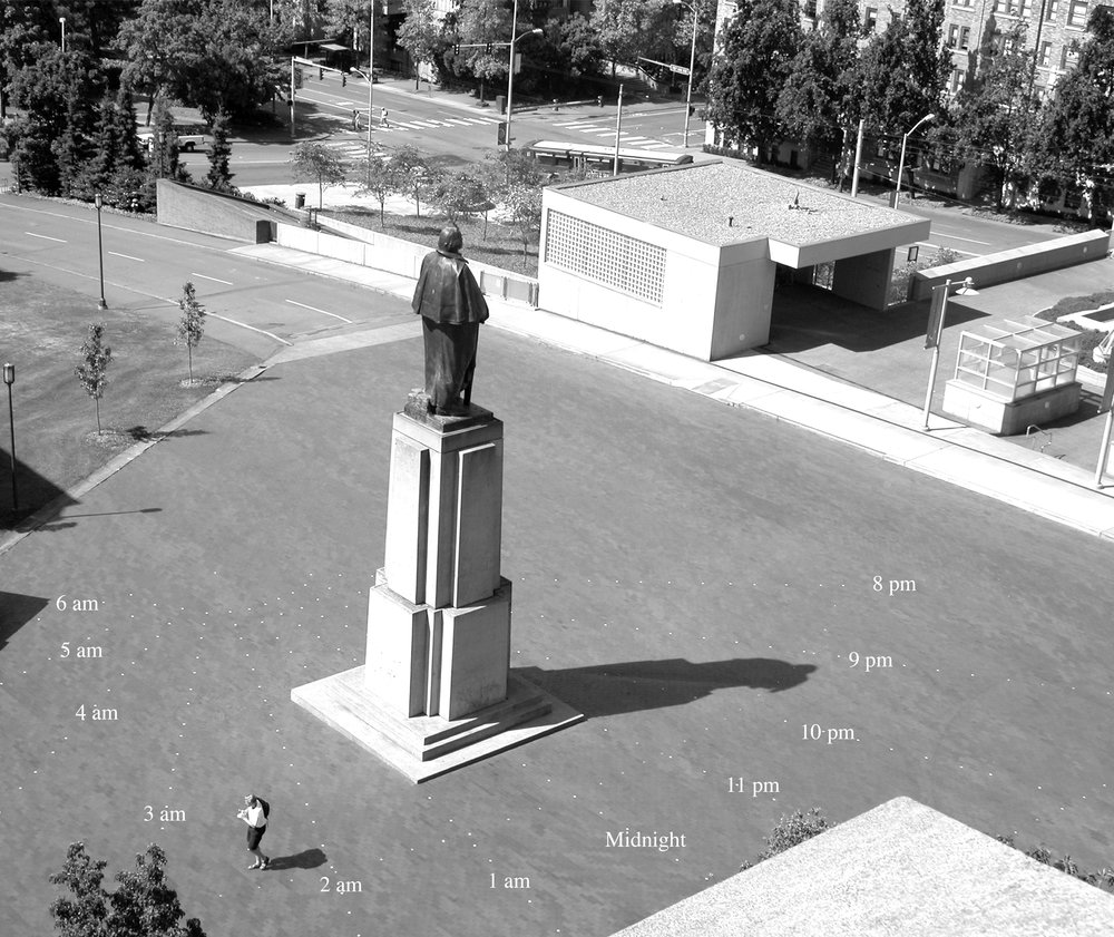 Baghdad by George, 10:10am Seattle, 9:10pm, Baghdad, 2003 (with Woody Sullivan)  Metal, paint, vinyl  This statue of George Washington on the University of Washington, Seattle campus was co-opted as the gnomon in this giant horizontal sundial; his head indicated the time in Baghdad as it crossed the yellow hour marker lines. Temporary installation for Spheres, the 2003 University of Washington Summer ARTS Festival, Seattle, WA.
