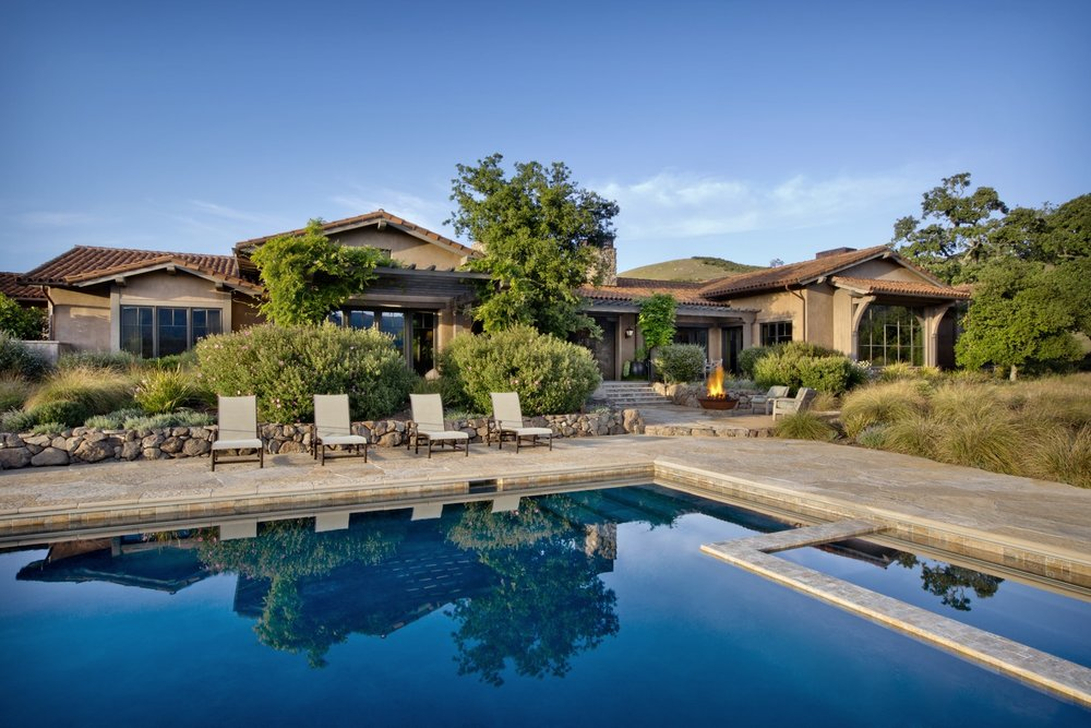 The pool reflects the blue sky, and the firepit was made from a reclaimed sugar bowl.