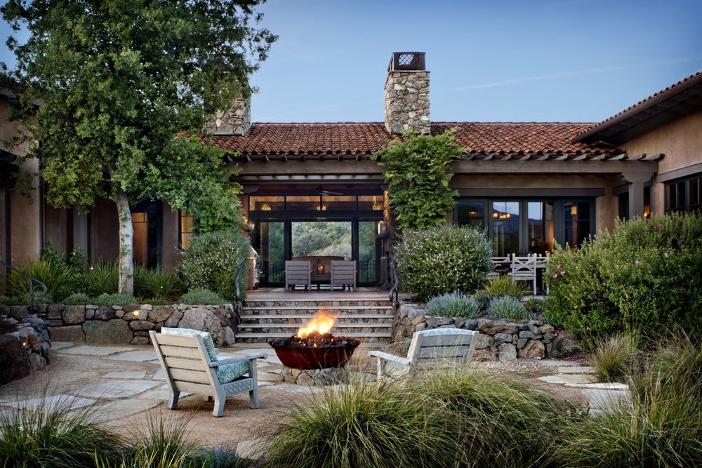 The buff-colored paving stones anchor a rustic seating area around the firepit.