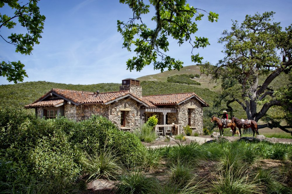 The guesthouse has a strong western theme, inside and out, with a hitching post creating the railing for the front porch.