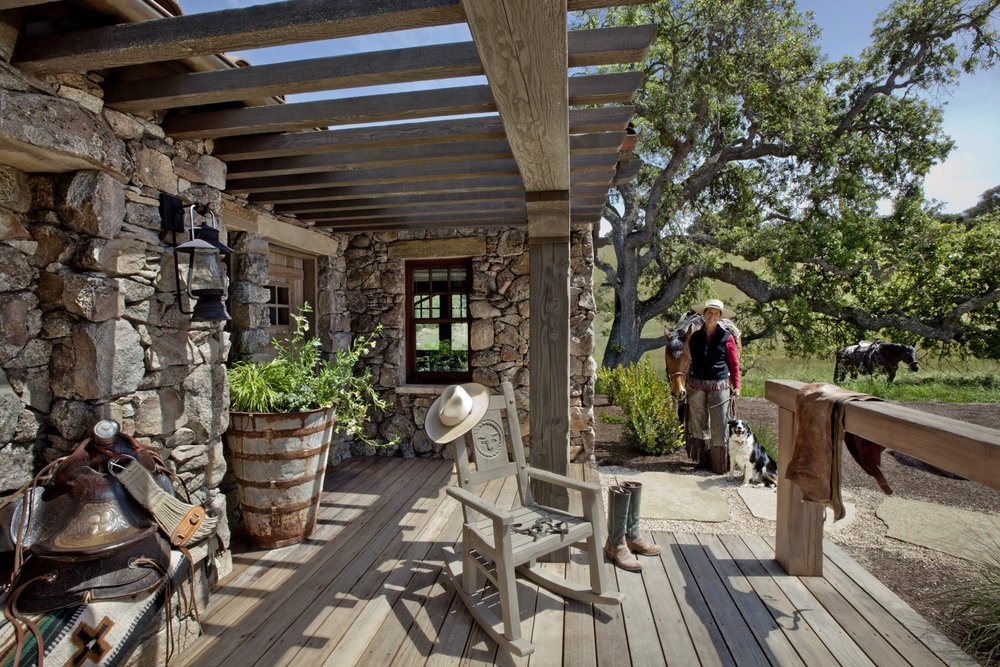 The ranch manager for the Santa Lucia Preserve is smiling with two horses and a dog, near the porch of the guesthouse.