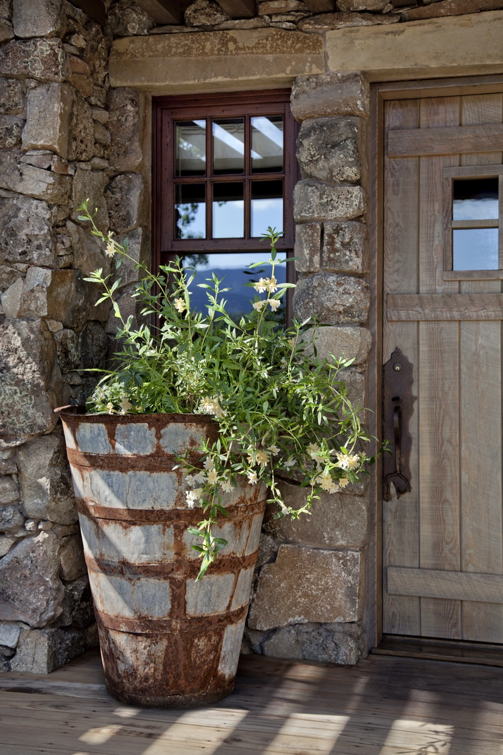 The guesthouse is covered in rustic, rough stone, and an old galvanized pot is a planter.
