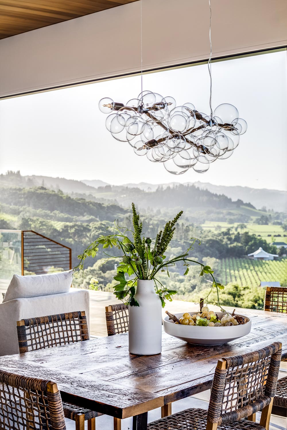 A rustic wood table holds elegant vases. under a dramatic light fixture, with hills and vineyards in the distance.