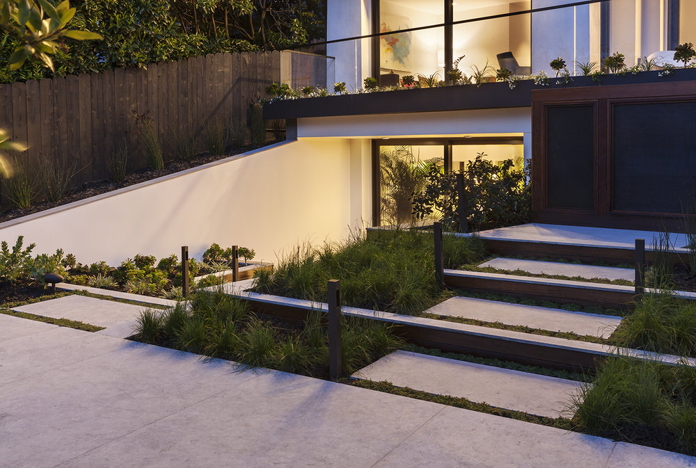 The lowest level is connected to the garden through plantings and a continuation of materials.