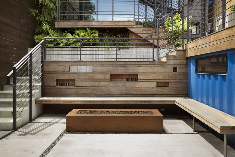 A corten firepit is surrounded by a wood bench and wall.