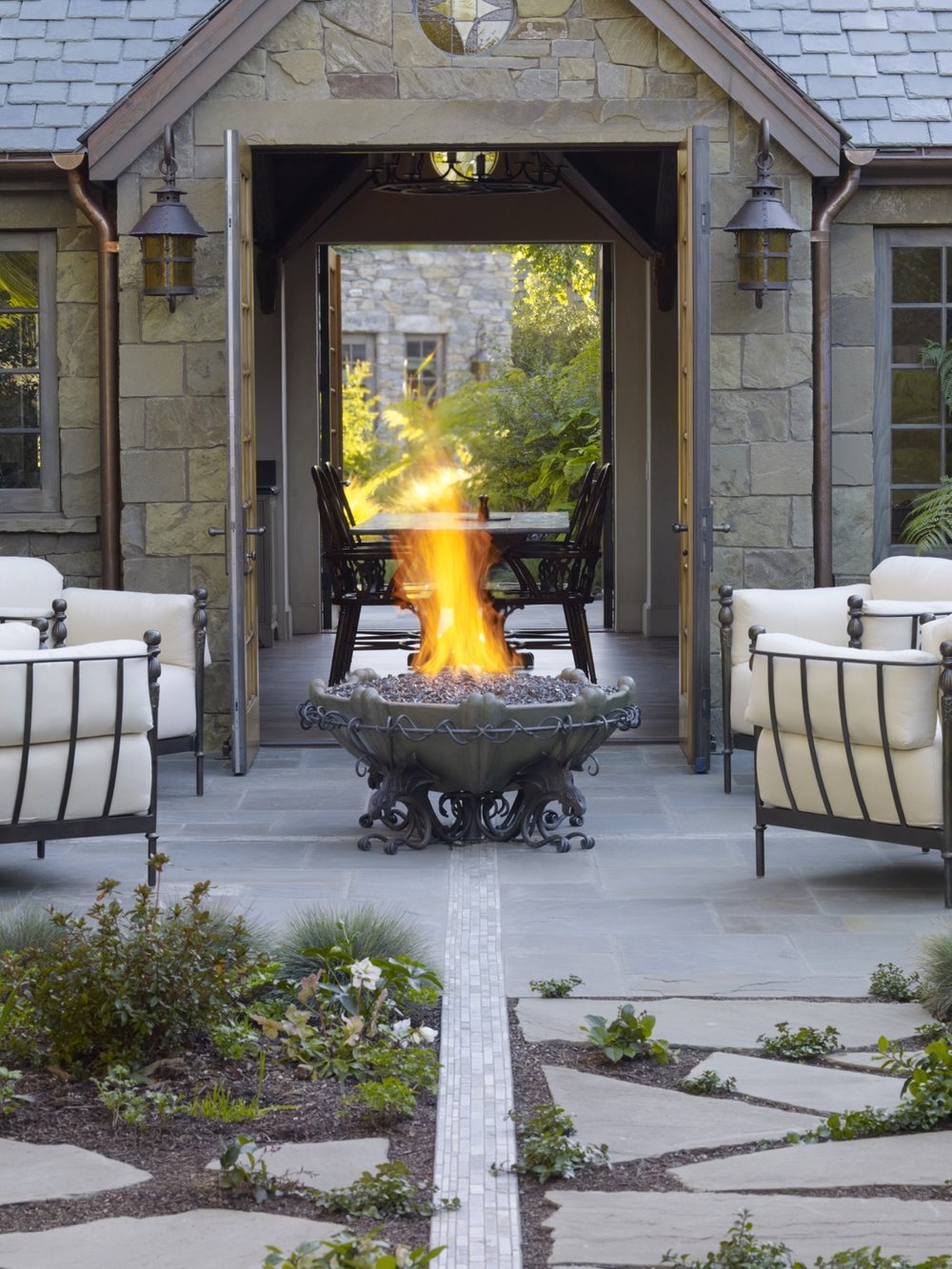 A fire pit anchors a courtyard outside of the dining room. On the other side of the open doors of the dining room, a water fountain anchors the entry courtyard.