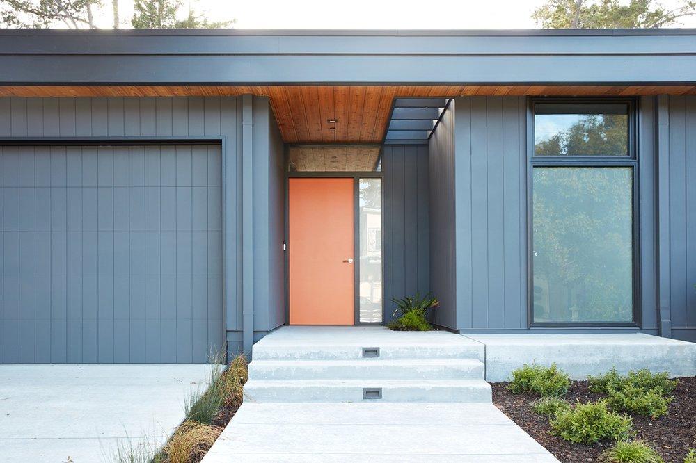 The front door is a pop of orange on a medium gray building.