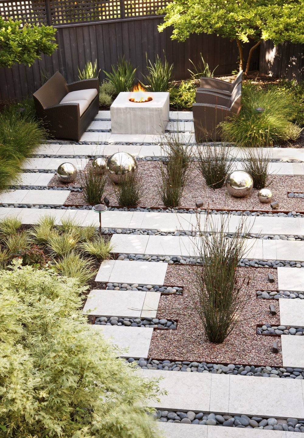 A concrete firepit is a gathering place in the far corner of the garden.