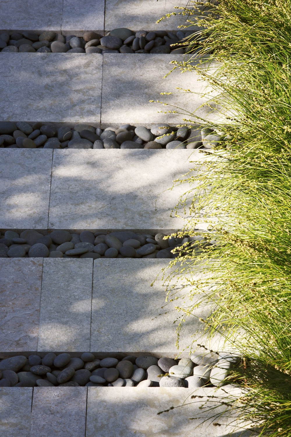 Bright green grasses contrast the greys of the stone and pebble paving.