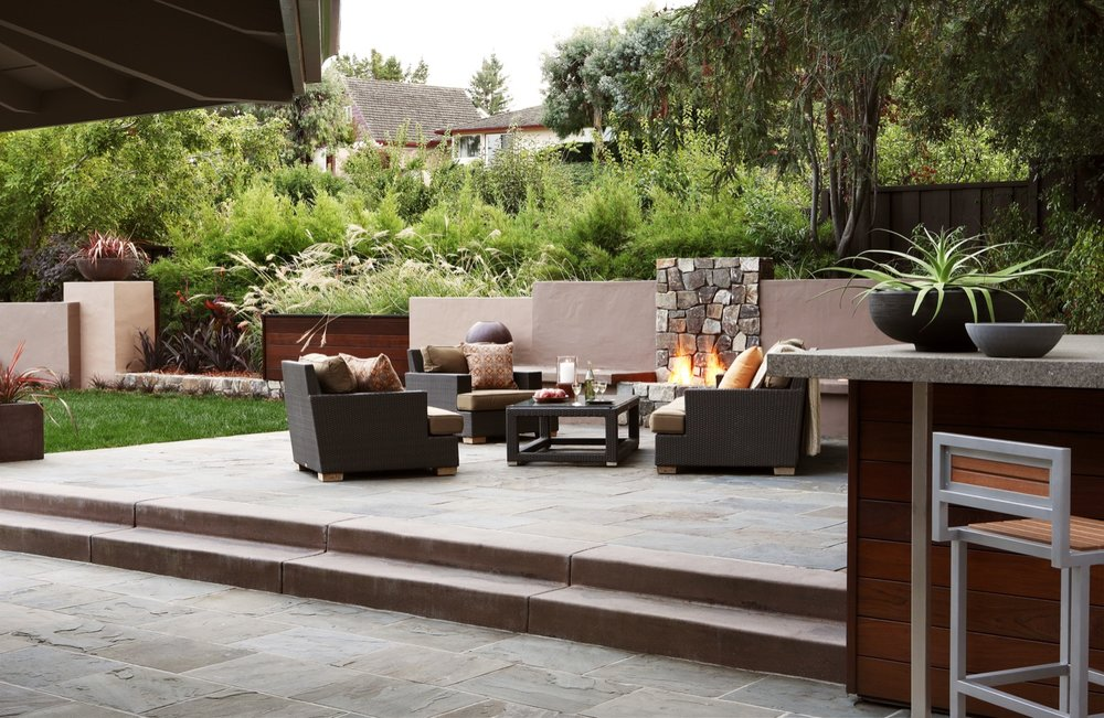 A stone fireplace anchors the seating area of the outdoor living room.