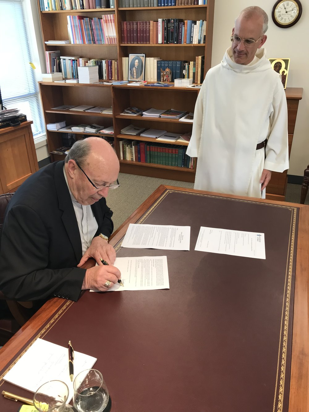 The Archbishop signs the decree of erection.