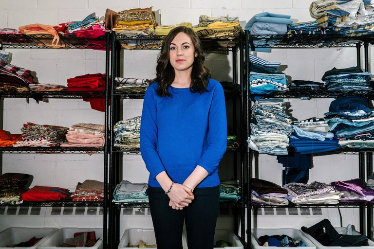 Jessica Schreiber, Founder of FABSCRAP, poses in front of fabric scraps in Jamaica, Queens Warehouse