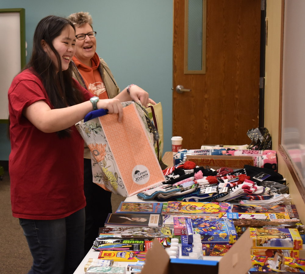Sophia and Brenda filling two comfort bags for children who have cancer and are undergoing chemotherapy at the December 2nd event.