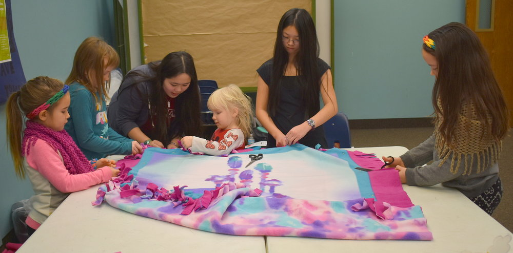 Five youth volunteers working with Sophia on tying a fleece blanket for a child who has cancer. This blanket was put in one of the comfort bags that was assembled on December 2nd.