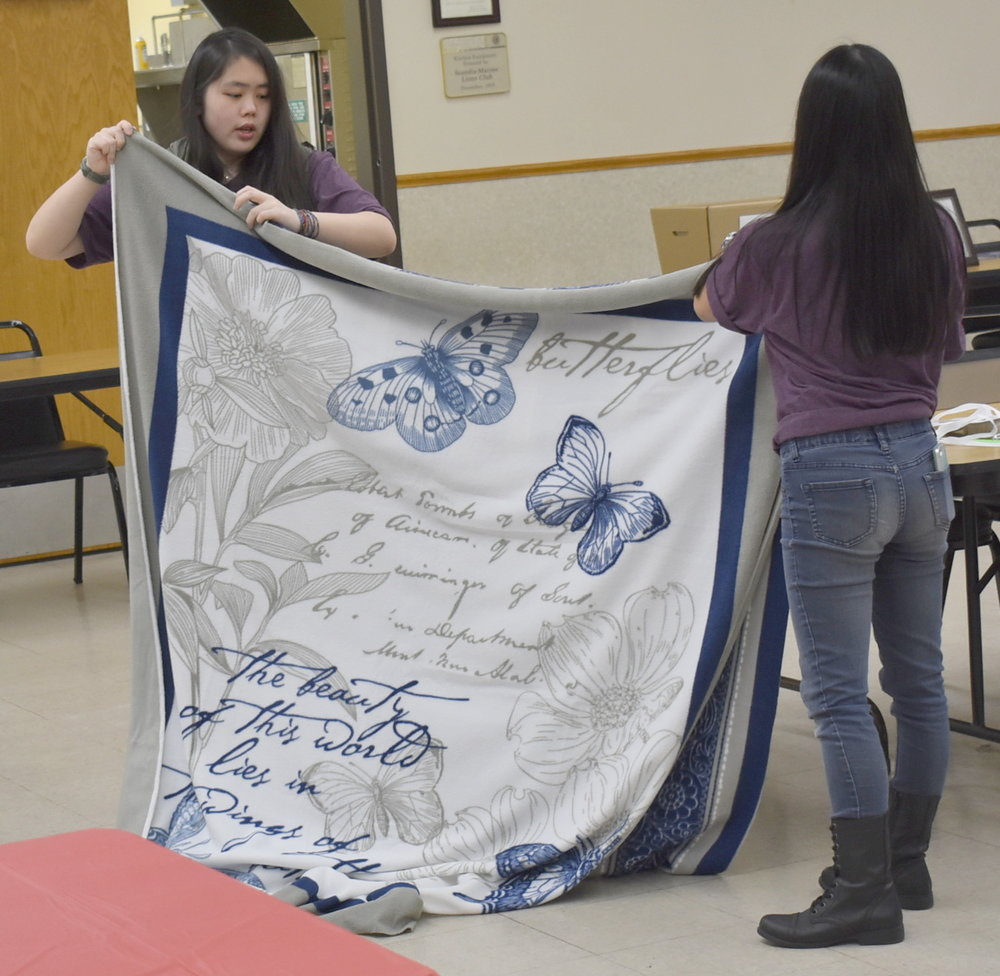 We are getting one of the fleece blankets ready to be cut so it can be tied at the One Stop Donation Drop. People from the community - youth and adults - tied the blankets. They were donated to Project Linus which distributes them to children and teens with life-threatening medical issues.