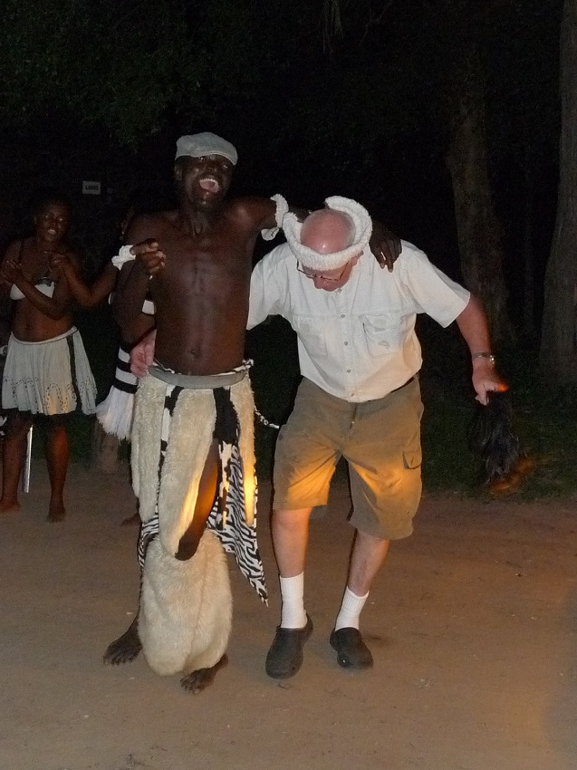Tourist dancing with traditional African dancers Victoria Falls.JPG