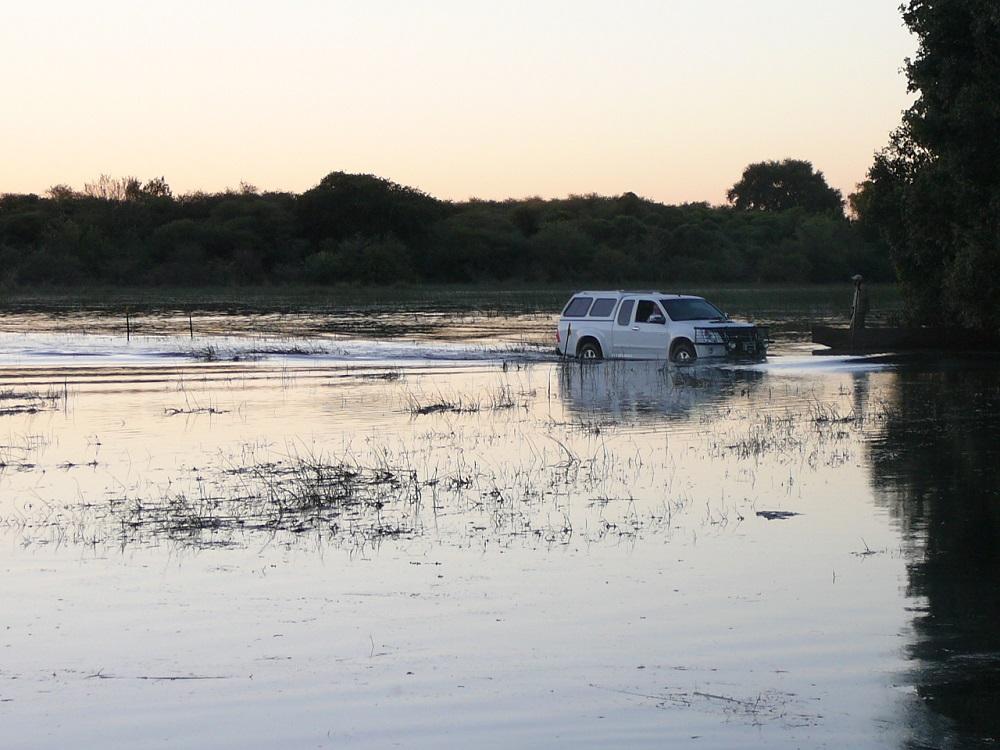 Vehicle and mokoro water sunset.JPG