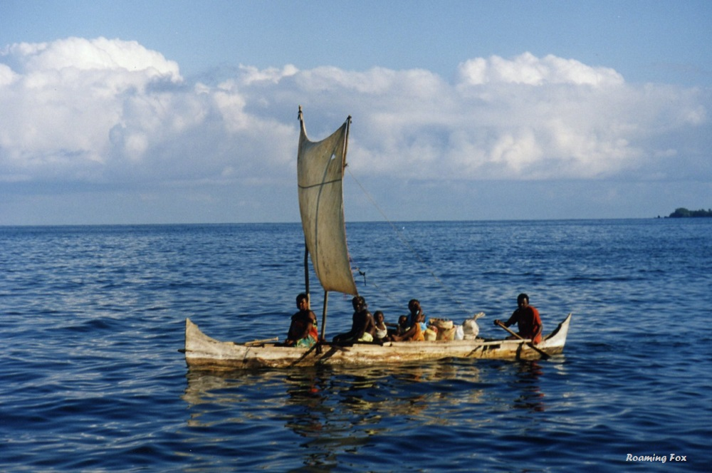 A family sailing in their pirogue from the mainland to their island