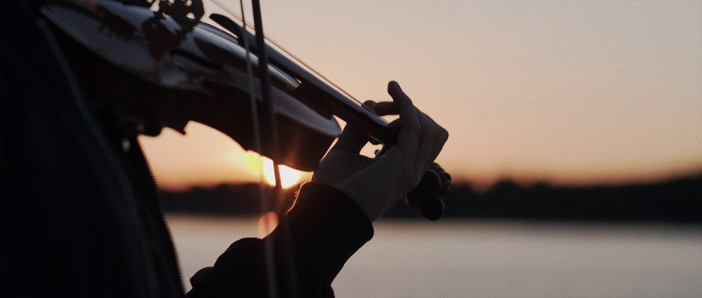 Violinist ob sončnem vzhodu