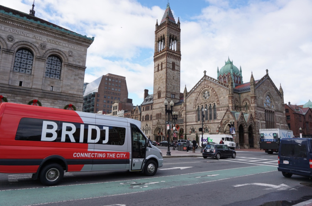 A Bridj van outside of The Boston Public Library. On-demand minibus transportation, on the rise in the Global North, mirrors a form of transport popular in the Global South.  (Photo by The Boston Herald)