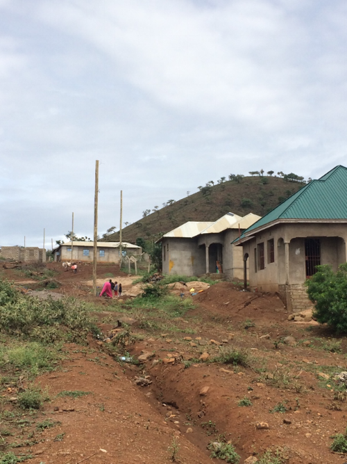 Household use of solar home systems even as the grid expands in peri-urban Arusha, Tanzania. Electricity poles are present, but there are no wires yet, so small solar home systems remain in use (roof of second house)  (Elise Harrington, March 2018)