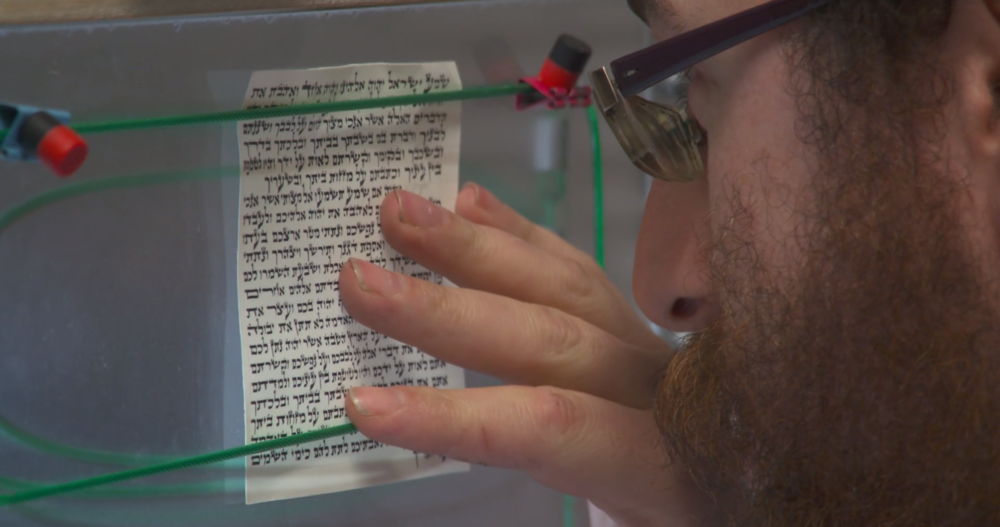 A scribe inspects a Mezuzah scroll