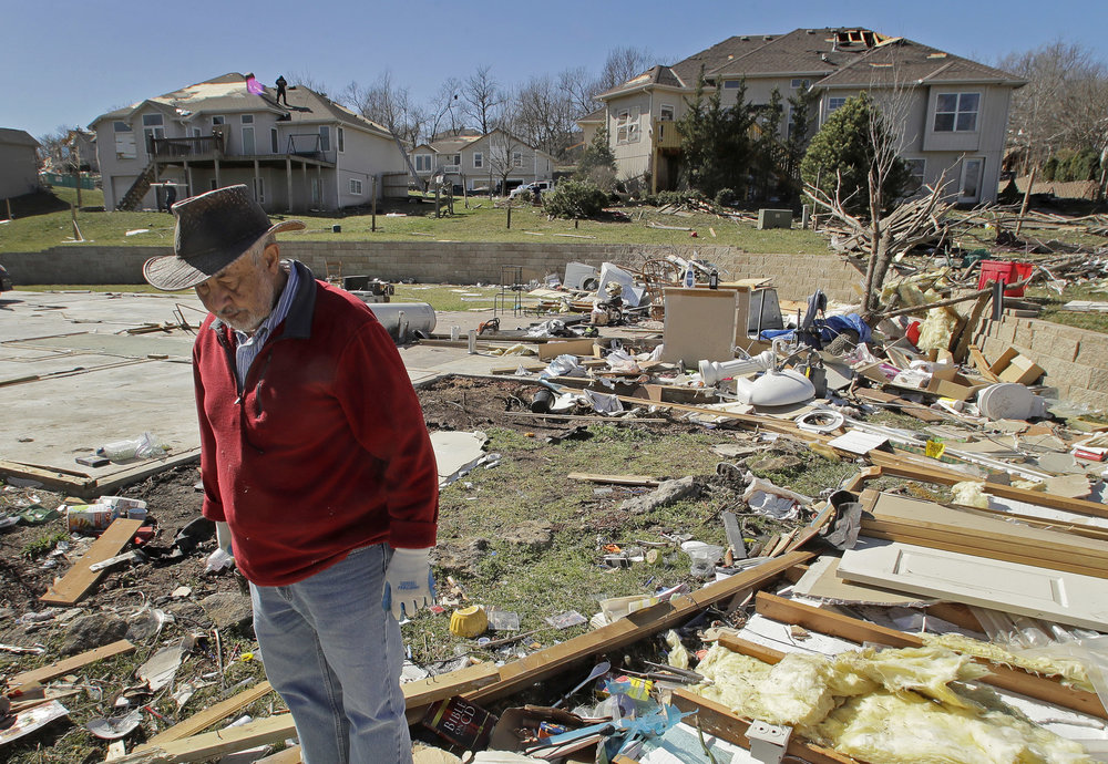FILE - In this March 7, 2017, file photo, Mark Swartz salvage items from his son's home that was destroyed by a tornado after a severe storm passed through Oak Grove, Mo. If you think this has been a wild and costly year for weather disasters, federal meteorologists say you are right, it's been record setting. So far this year the United States has had 15 weather disasters that caused at least $1 billion in damages. (AP Photo/Charlie Riedel, file)