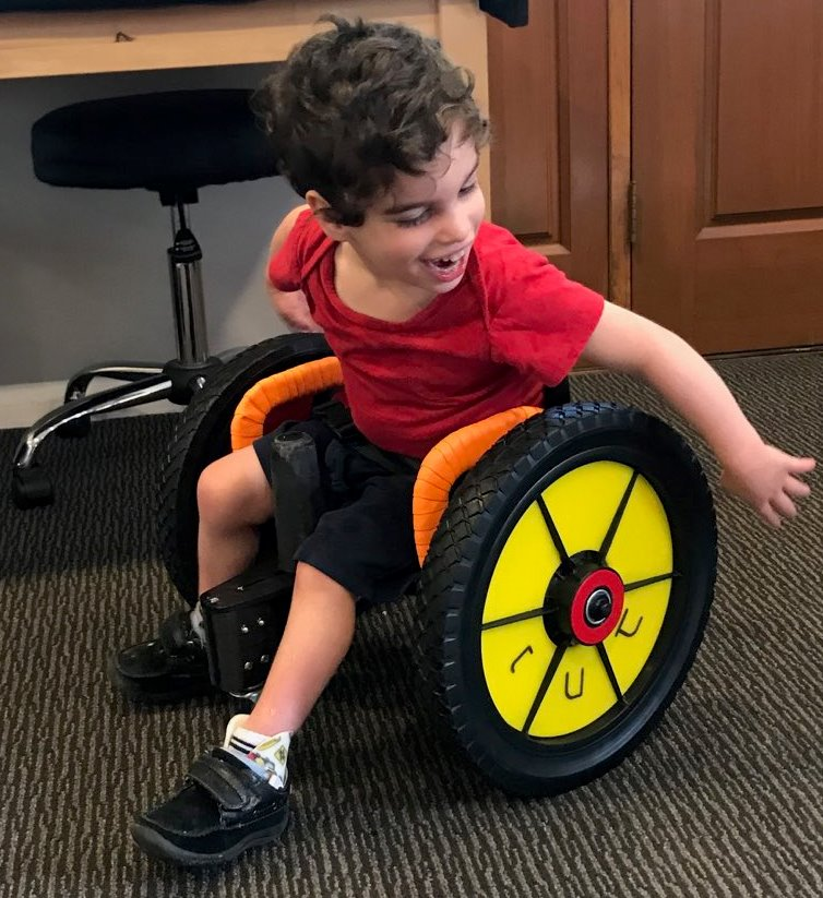 Three-year-old Nesenal takes his new combo scooter for a spin.  It was designed by lady engineering students at Johns Hopkins to allow him to sit upright (with back support & pommel) or lay on his belly and push with his legs.  Nesenal has cerebral palsy causing low tone.  He needed an indoor scooter to keep up with his siblings.