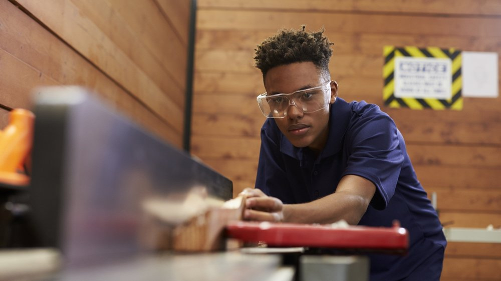 Boy with protective goggles cuts wood in workshop