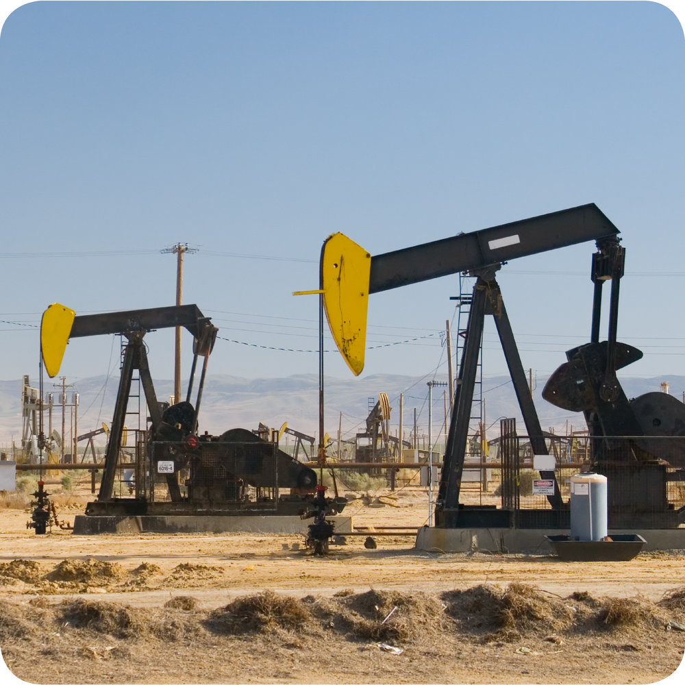 Two pumpjacks in an oil field.