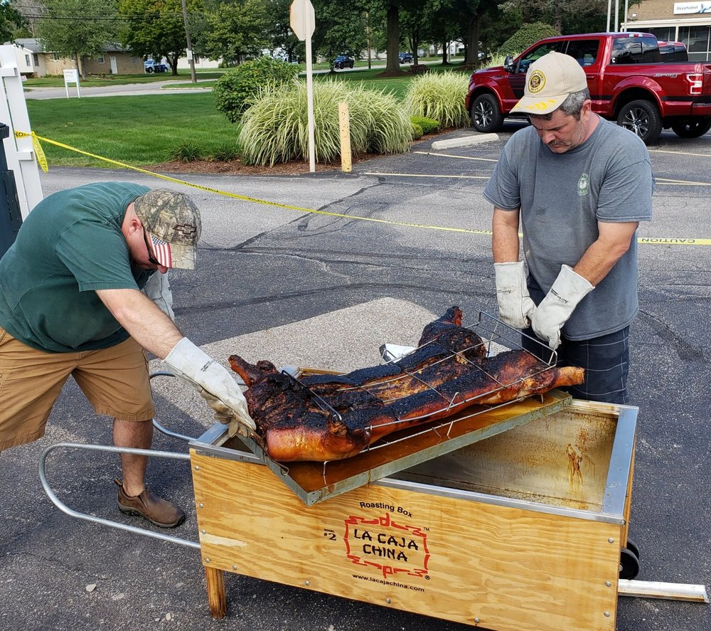 Trustees Nate Moore and Hank Nest worked hard to prepare the pig.