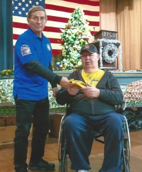 Pictured is Butch Bost, PER presenting a pair of wheel chair gloves to one of the many Veterans in attendance.