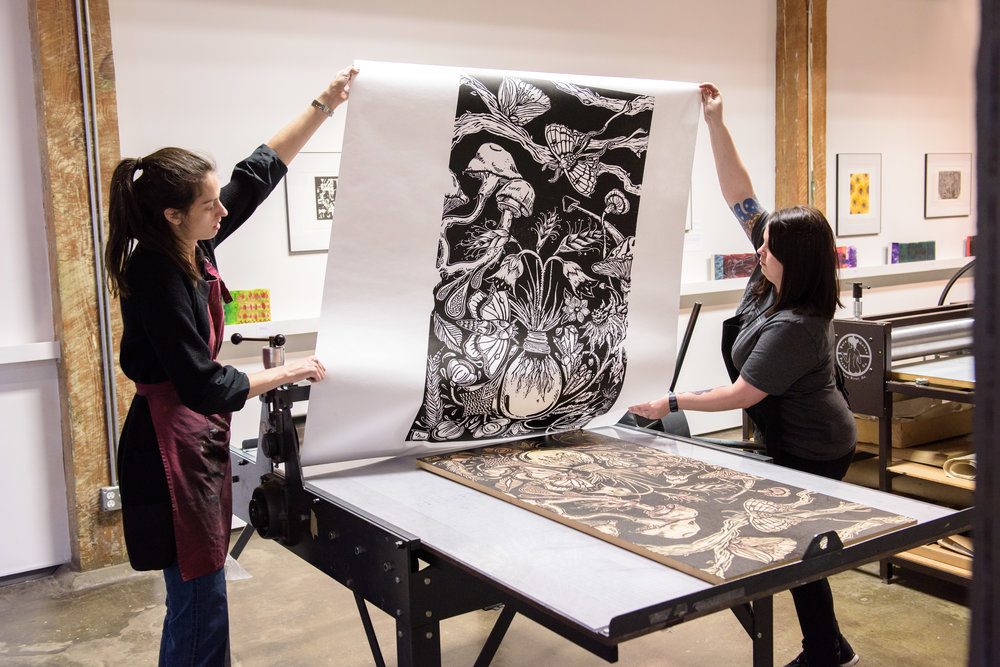 Education Director Alexa Healey helping artist Van Lango print her woodblock