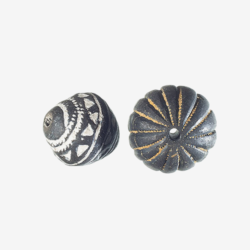 "Mali Hand-Stamped Clay Spindle Whorls   Material: Clay   Mali hand-stamped clay beads were originally used as spindle whorls for spinning wheels, and were used to spin cotton, wool, yarn and other threads. Modern replicas come in a variety of shapes but are individually carved and stamped with traditional decorations, geometric patterns and designs. Once the beads are fired, they are dipped into a white chalk, now often ground freshwater shells, which gives the indented carved patterns a white color.  Any excess white is wiped off of the bead before it dries on the colored part.  These beads are often black, dark brown, or light brown, depending on the type of clay that is used to make them. The clay is pounded and sieved into finer and finer pieces and pieces of old clay pots are often added to the clay mixture for additional ""strength."""